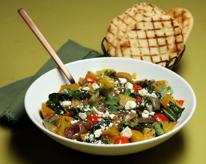 Grilled golden beets center a fall salad that makes a colorful dinner, with sauteed beet greens, red onions, bell pepper, herbs and crumbled feta. (Terrence Antonio James/Chicago Tribune/TNS)
