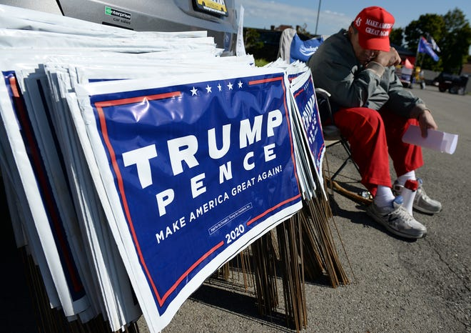 Beaver County Republican Party Vice Chairman Ralph Flare of Pulaski Township sits waiting to give out Trump/Pence yard signs during a Trump Pop-Up merchandise event on Saturday in the parking lot of the Trinity Building in Beaver.