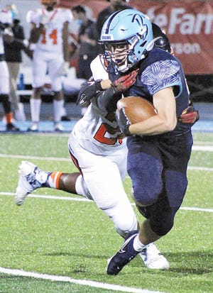 Bartlesville High senior runningback Dylan McCoy fights through a potential tackle during last Friday's football showdown against Tulsa Washington.