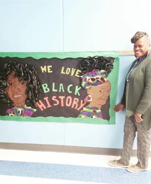 Margie Kidd stands in front of a bulletin board that was made last year for her and fellow teacher Patricia Moye by coworker Courteney Simmons. Kidd, who loved African American history, recently died of COVID-19 complications.