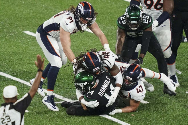 Denver Broncos A.J. Johnson (45) and Josey Jewell (47) sack New York Jets quarterback Sam Darnold during the second half of Thursday's game in East Rutherford, New Jersey. [JOHN MINCHILLO / ASSOCIATED PRESS]