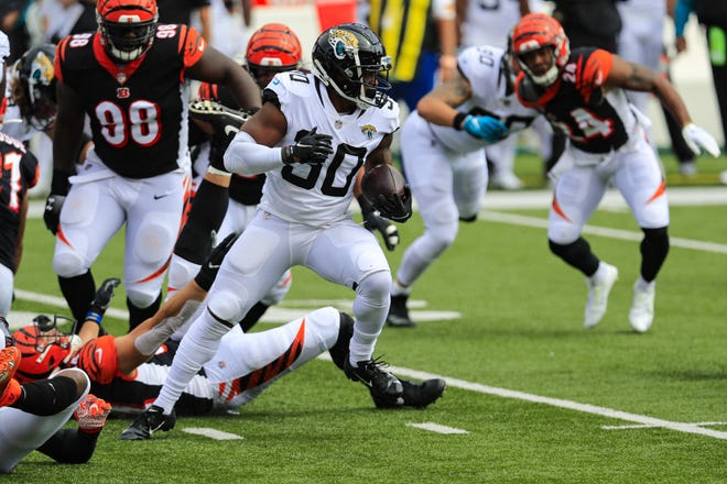 Jaguars running back James Robinson (30) looks for room against the Bengals defense on Sunday at Paul Brown Stadium.