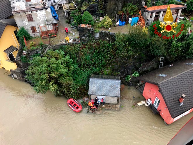 Firefighters evacuate people from a house amid flooding in the town of Ornavasso, in the northern Italian region of Piedmont.