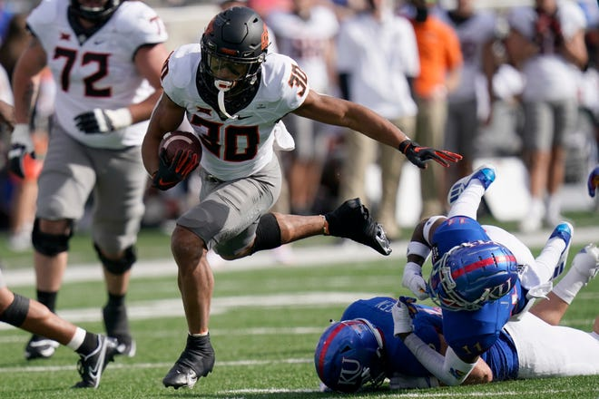 Oklahoma State running back Chuba Hubbard (30) breaks away from Kansas cornerback Johnquai Lewis (11) during the first half of an NCAA college football game in Lawrence, Kan., on Saturday.
