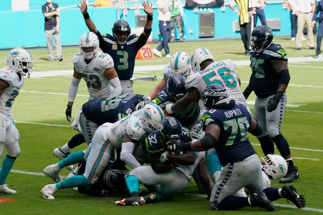 Seattle Seahawks running back Chris Carson (32) scores a touchdown during the second half against the Miami Dolphins on Sunday in Miami Gardens. The Seahawks defeated the Dolphins 31-23.(AP Photo/Lynne Sladky)