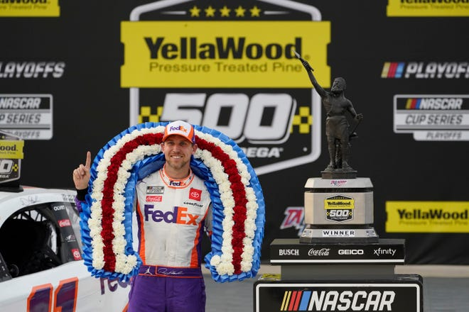 Denny Hamlin poses with the trophy after winning the NASCAR Cup Series race at Talladega Superspeedway on Sunday in Talladega, Ala.