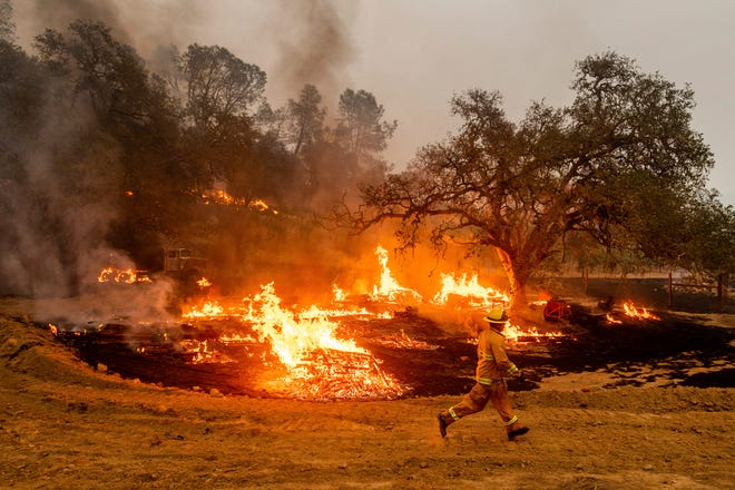 A firefighter runs past flames while battling the Glass Fire in a Calistoga, Calif., vineyard Thursday. Deadly wildfires in California have burned more than 4 million acres (6,250 square miles) this year — more than double the previous record for the most land burned in a single year in the state.