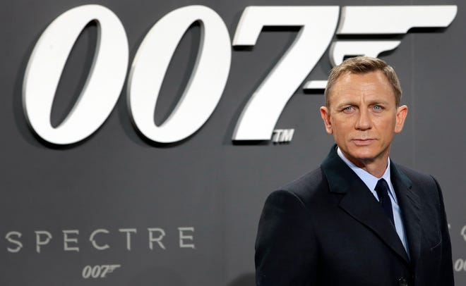 """FILE - This is a Wednesday, Oct. 28, 2015 file photo of actor Daniel Craig poses for the media as he arrives for the German premiere of the James Bond movie """"Spectre"""" in Berlin, Germany. The release of the James Bond film """"No Time to Die"""" has been delayed again, this time to 2021, because of the effects of COVID-19 on the theatrical business. MGM, Universal and Bond producers, Michael G. Wilson and Barbara Broccoli, said on Twitter Friday that the 25th instalment in the franchise will now open globally on April 2, 2021. (AP Photo/Michael Sohn, File)"""
