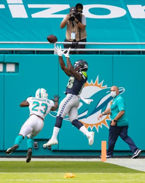 Seahawks wide receiver David Moore pulls in a 17-yard touchdown catch over Dolphins cornerback Noah Igbinoghene late in Sunday's game at Hard Rock Stadium.