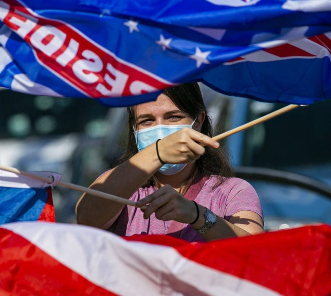 Kamilah Acebal, 27, waves a Joe Biden and a Cuban flag before the start of a Cubans Con Biden caravan at Bright Park in Hialeah on Sept. 19. [MATIAS J. OCNER/THE MIAMI HERALD]