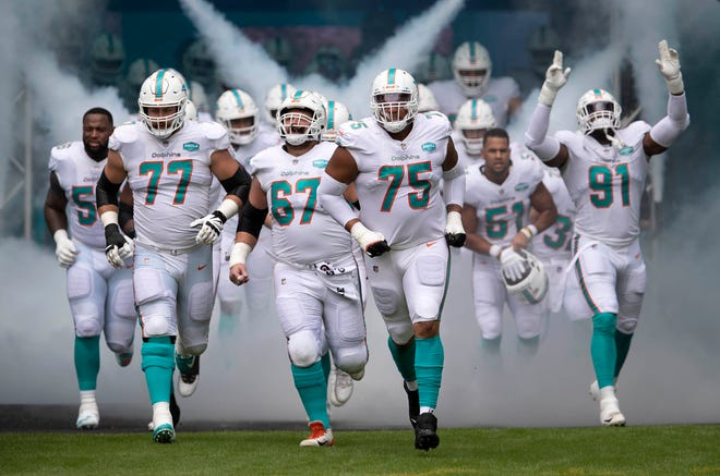 Dolphins offensive tackle Jesse Davis (77), center Ted Karras (67), and guard Ereck Flowers lead players onto the field at Hard Rock Stadium for a game against Seattle.
