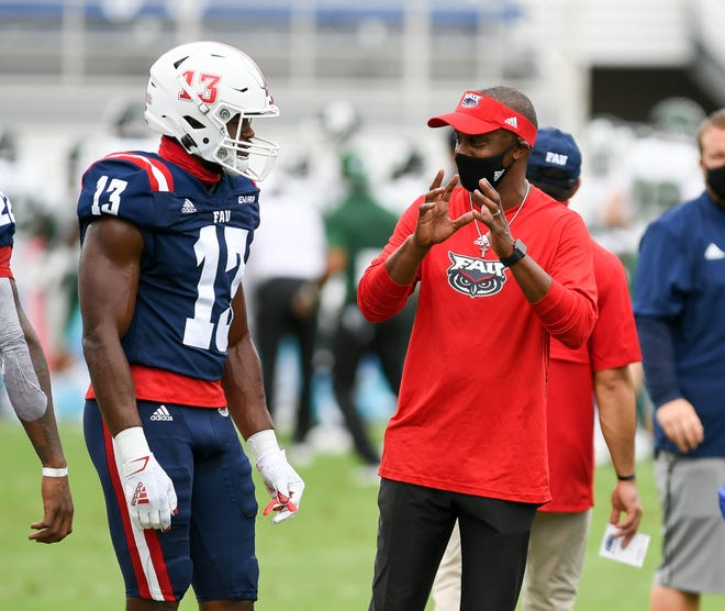 Florida Atlantic  head coach Willie Taggart, right, talks with linebacker Leighton McCarthy before a 21-17 win over Charlotte on Saturday. McCarthy was named Conference USA Defensive Player of the Week after recording 10 tackles and three sacks.