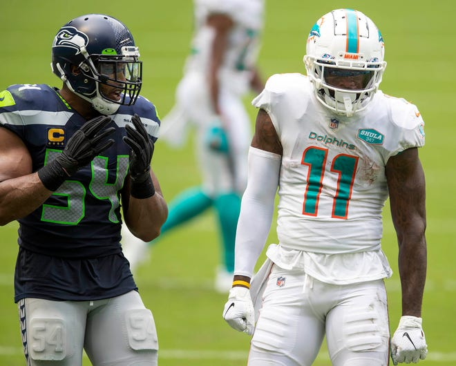 Miami Dolphins wide receiver DeVante Parker (11) celebrates a first down as Seattle Seahawks middle linebacker Bobby Wagner (54) looks on at Hard Rock Stadium in Miami Gardens, October 4, 2020.  [ALLEN EYESTONE/The Palm Beach Post]