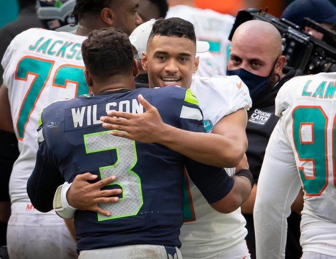 Seahawks quarterback Russell Wilson and Dolphins quarterback Tua Tagovailoa embrace following Sunday's game.