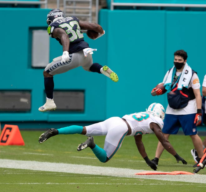 Seattle Seahawks running back Chris Carson (32) leaps over Miami Dolphins cornerback Noah Igbinoghene (23) who was attempting a tackle at Hard Rock Stadium in Miami Gardens, October 4, 2020.  [ALLEN EYESTONE/The Palm Beach Post]