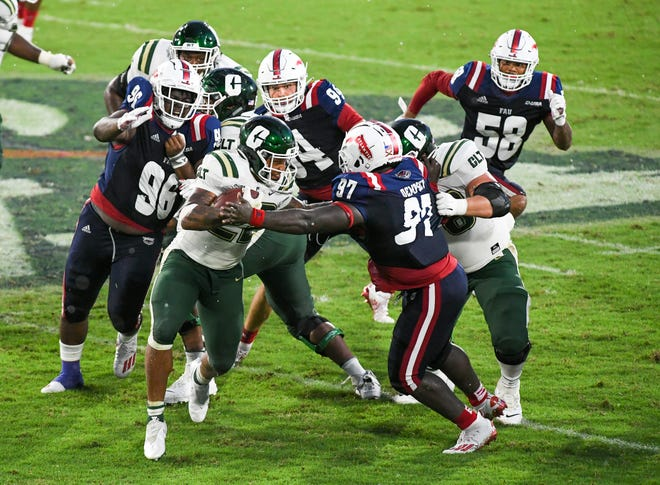 Florida Atlantic players make a stop during a 21-17 win over Charlotte on Oct. 3 in Boca Raton.