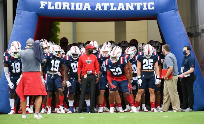 Florida Atlantic head coach Willie Taggart and his team prepare to take the field before game against Charlotte on October 3. FAU won 21-17, but that's the only game it's played this season.