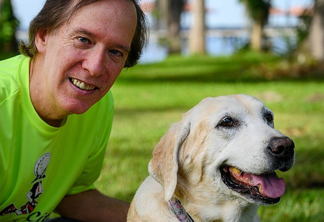 Gary Williams poses with his 12-year-old yellow Labrador, Guenevere in the backyard of their home on Friday.