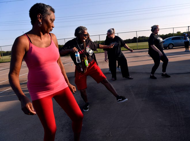 """Connie Sells (left), Brenda Walker and others line dance Saturday at Stevenson Park. """"Unity in the Community"""" promoted togetherness, bringing people together to share culture and music. Walker also was dancing because it was her birthday."""