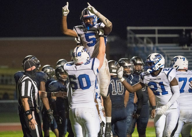 Williamstown's Turner Inge is hoisted by teammate Devin Cope after Inge scored a touchdown during the 4th quarter of the football game between Williamstown and Timber Creek, played at Timber Creek High School on Saturday, October 3, 2020.  Williamstown defeated Timber Creek, 21-0.
