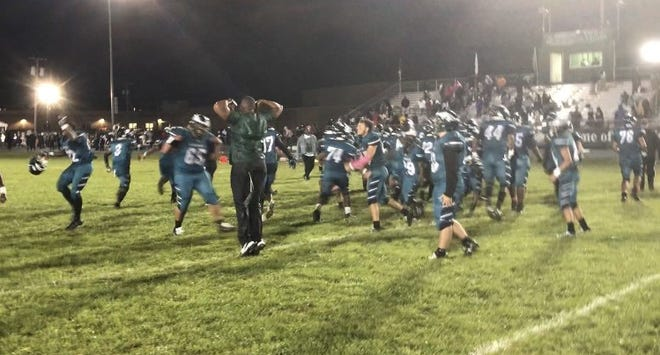 The Winslow High School football team celebrates its 15-12 upset win over No. 5 Camden on Saturday night.