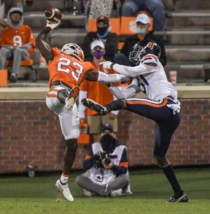 Clemson corner back Andrew Booth Jr. makes a one-handed interception while holding off Virginia wide receiver Lavel Davis Jr. last October in Memorial Stadium.