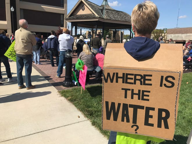 """Jill Robbins, a Lake Freeman homeowner, wears a sandwich board reading, """"Where is the water?"""" during a Saturday, Oct. 3, 2020, rally in downtown Monticello aimed at getting federal regulators' attention over low water levels this summer."""