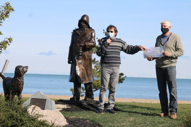 "Rich Norgard, president of the Port Clinton Lighthouse Conservancy, presents a $47,000 check to artist Andy Sacksteder for the purchase of ""The Lightkeeper"" sculpture."