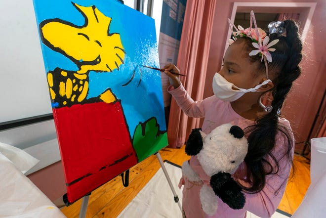 """Kaley Williams, 8, paints a panel of a """"Peanuts"""" mural that will be placed in the outpatient pediatric floor of One Brooklyn Health at Brookdale Hospital, Thursday, Oct. 1, 2020, in the Brooklyn borough of New York. The virus pandemic won't stop Charlie Brown, Snoopy or the """"Peanuts"""" gang from marking an important birthday and they're hoping to raise the spirits of sick kids while they celebrate. The beloved comic marks its 70th anniversary this week with new lesson plans, a new TV show and a philanthropic push that includes donating """"Peanuts"""" murals for kids to paint in 70 children's hospitals around the globe, from Brooklyn to Brazil. (AP Photo/Mary Altaffer)"""