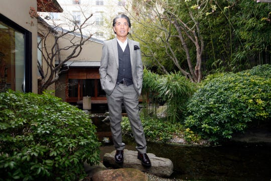 In this Tuesday, March 24, 2009 file photo, Japanese fashion designer Kenzo Takada poses outside his Paris house.