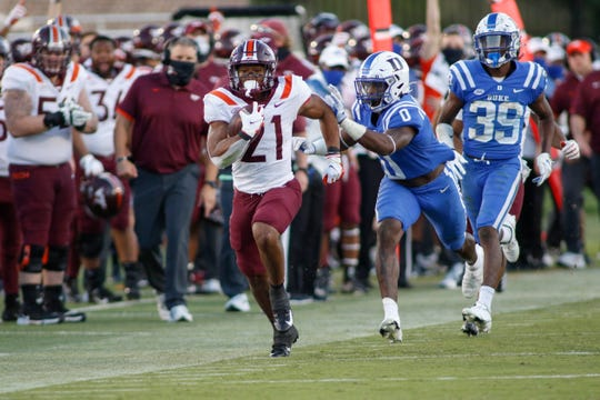 Hokies running back Khalil Herbert breaks free for a first down ahead of Blue Devils safety Marquis Waters (0) and cornerback Jeremiah Lewis (39).