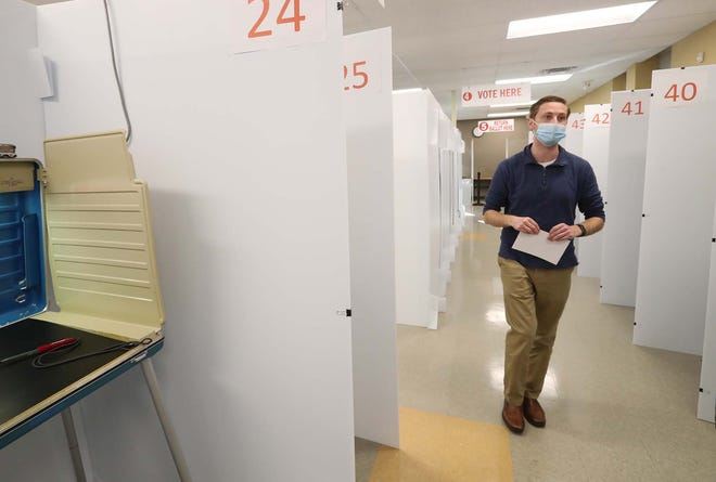 Lance Reed, director of the Summit County Board of Elections, walks through the early voting center that is set up with COVID-19 precautions. A private vendor is taking too long to get absentee ballots to voters in Summit County. So election officials will do it themselves.