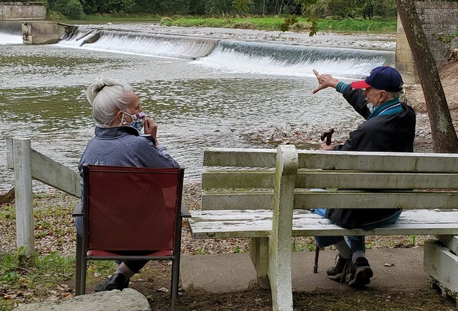 Mary Starbuck and Terry Woods of the Canal Society of Ohio discuss the history of Six Mile Dam. The box-like structure on the downstream side of the dam is a flood control mechanism added in 1941, to the right of that is a fish ladder. The right end of the dam is noticeably lower due to undermining.