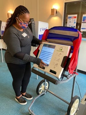 Jasper County Election and Voter Registration director Jeanine Bostick demonstrates how an in-person absentee voting machine works at her office Friday. The machine being used for curbside voting.