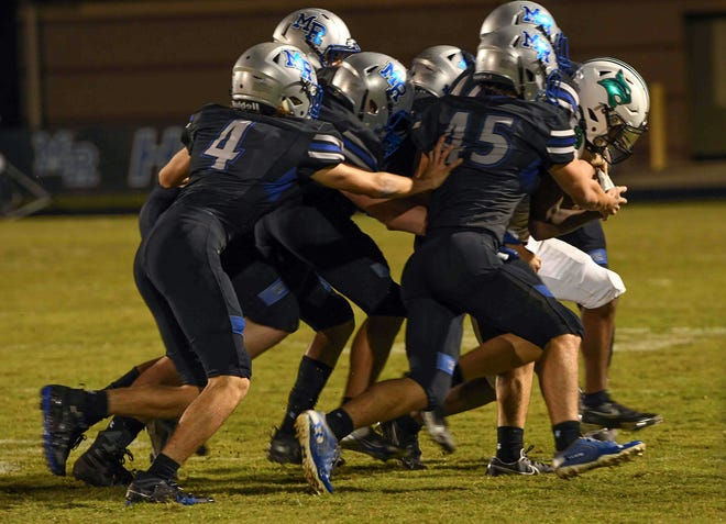 May River defenders try to bring down a Bluffton runner Friday night.