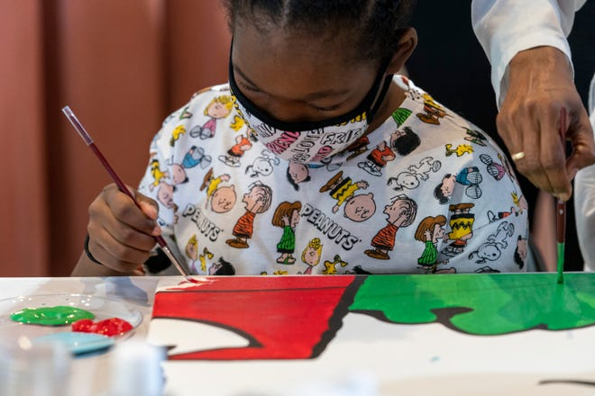 "Kerrin McCarthy, 14 , paints a panel of a ""Peanuts"" mural that will be placed in the outpatient pediatric floor of One Brooklyn Health at Brookdale Hospital, Thursday, Oct. 1, 2020, in the Brooklyn borough of New York. [Mary Altaffer/The Associated Press]"