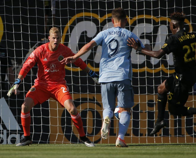 Columbus Crew SC goalkeeper Jon Kempin (24) watches the ball off the foot of Sporting Kansas City forward Krisztian Nemeth (9) beind defended by Columbus Crew SC defender Harrison Afful (25) during the first half of the MLS soccer match at MAPFRE Stadium in Columbus on Sunday, June 23, 2019. [Adam Cairns/Dispatch]