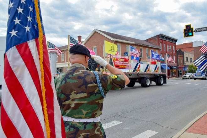 Staff Sgt. Tim Peterson salutes the vehicles in the Trump parade as they go by the courthouse.