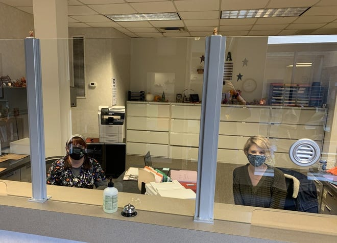 Wayne County Employee Health Clinic Supervisor Misty White and receptionist Jill Killinger sit behind the plexiglass shield installed at the clinic using CARES Act money. The county has used the federal funds to pay for personal protective equipment and other COVID-19 items.