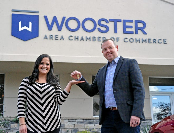 Samira Zimmerly, the new head of the Wooster Area Chamber of Commerce, accepts the keys to the Chamber from Justin Starlin, the outgoing chamber head.