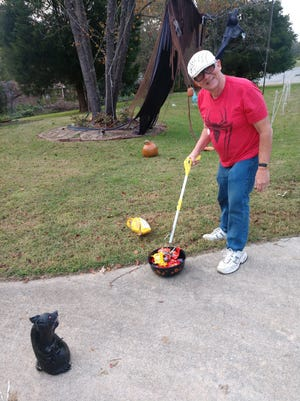 Mike Savicki, also known as Mr. Halloween, demonstrates the no-contact candy distribution system he devised using a grabber for Halloween night. In the photo, he pretends to be feeding his pet rat. Other Halloween decorations that he displays in his front yard are seen behind him. Savicki will add Halloween displays right up to the night before Halloween.