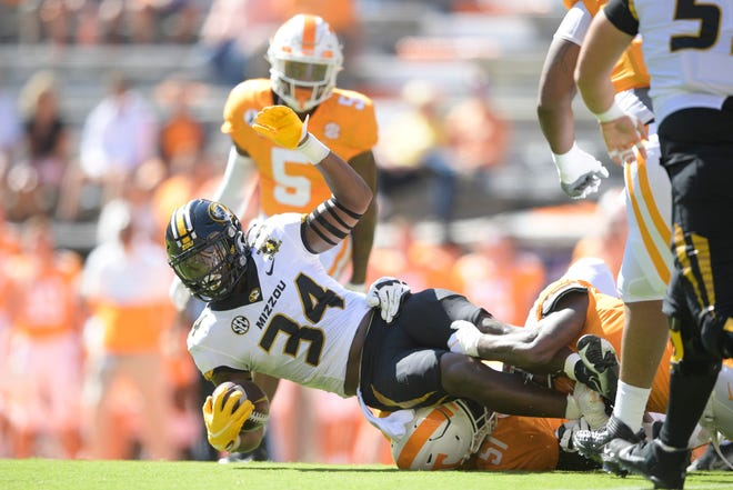 Missouri running back Larry Rountree III (34) is tackled by Tennessee defensive back Trevon Flowers (1) during the first quarter of Saturday's game at Neyland Stadium.