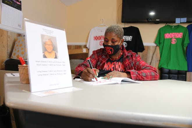 """Quarla Blackwell writes down notes inside her Q Bizzle Creations office on Queen Street Monday, Oct. 5, with a photo of Evernell """"Nell"""" Pittman, who was bruttaly attacked with a baseball bat in January, on her desk. [Brandon Davis/Kinston Free Press]"""