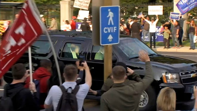 In this image from video, President Donald Trump waves as he drives past supporters gathered outside Walter Reed National Military Medical Center in Bethesda, Md., Sunday, Oct. 4, 2020. Trump was admitted to the hospital after contracting COVID-19.