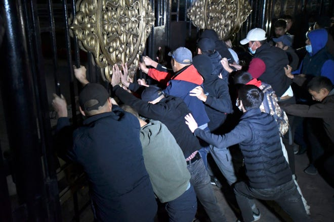 People try to storm the gate into the government headquarters during a rally against the results of a parliamentary vote in Bishkek, Kyrgyzstan, on Monday. Large crowds of people gathered in the center of Kyrgyzstan's capital to protest against the results of a parliamentary election, early results of which gave the majority of seats to two parties with ties to the ruling elites amid allegations of vote buying.