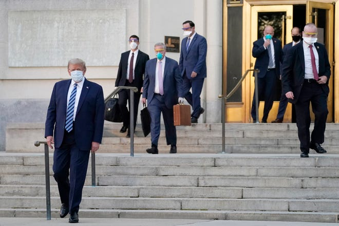 President Donald Trump, left, walks out of Walter Reed National Military Medical Center on Monday to return to the White House after receiving treatments for COVID-19.
