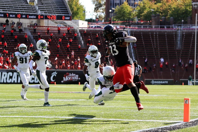 South Florida defensive back Vincent Davis (3) attempts to tackle Cincinnati running back Gerrid Doaks (23) as he scores a touchdown Saturday in Cincinnati.
