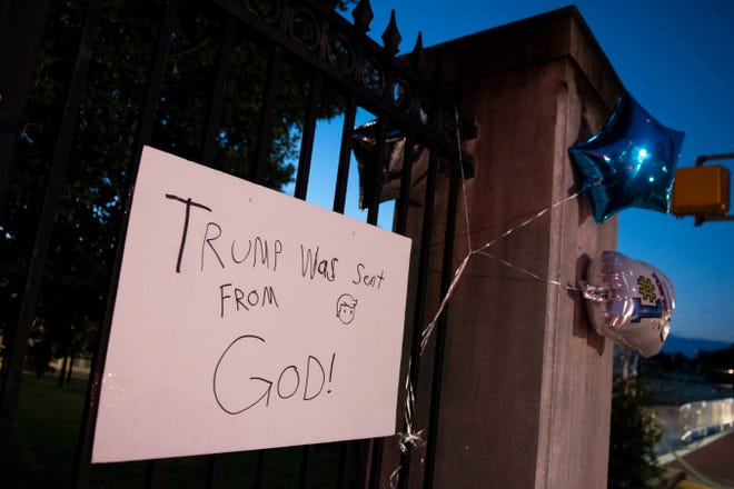 A sign on the fence at the entrance to Walter Reed National Military Medical Center in Bethesda, Md., on Monday morning. President Donald Trump was admitted to the hospital after contracting the coronavirus.