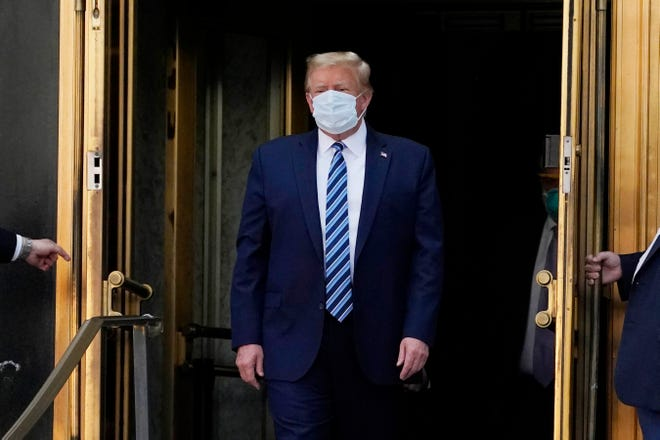 President Donald Trump walks out of Walter Reed National Military Medical Center to return to the White House after receiving treatments for covid-19, Monday, Oct. 5, 2020, in Bethesda, Md. (AP Photo/Evan Vucci)