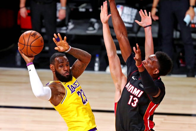 The Lakers' LeBron James (23) passes the ball against  Miami's Bam Adebayo (13) during the third quarter of Game 1 of the NBA Finals. [Kim Klement-USA TODAY Sports]